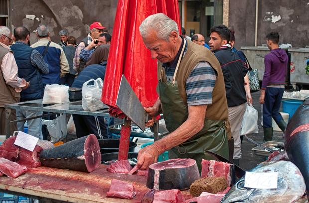 Stallholder in Catania fish market, Sicily, Italy